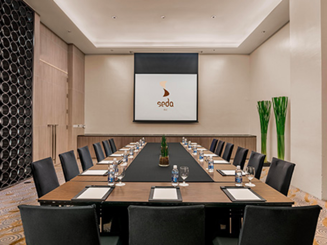 hotel conference room with projector screen; memo on table
