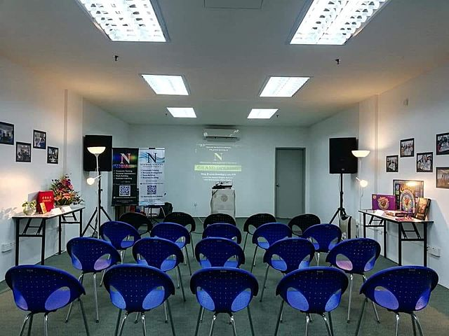 small workshop room in penang with blue chairs and speakers