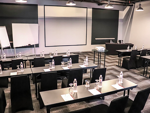 meeting room with classroom layout facilitated with projector screen and drinks