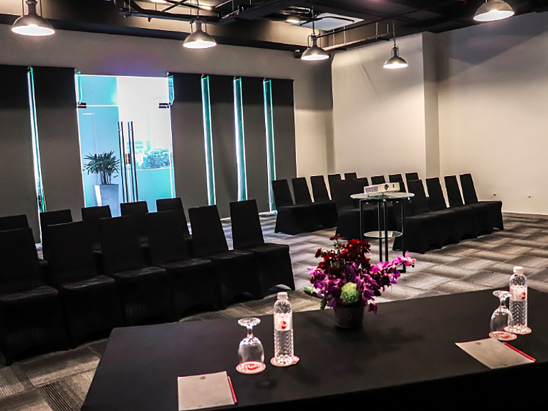 function room for seminar with black audience chairs and drinks