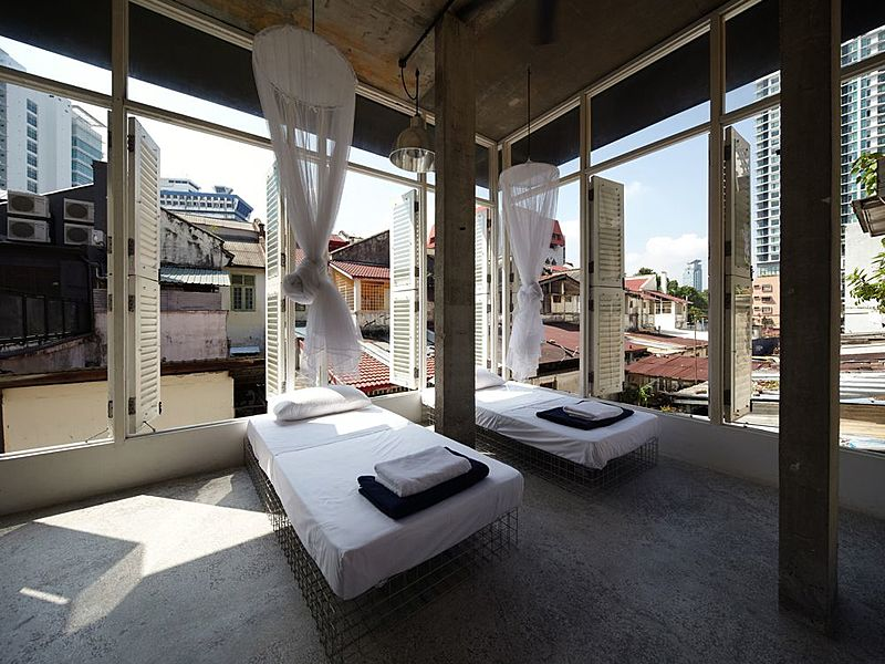boutique hotel room in kuala lumpur with large windows and bed nets