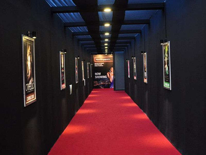 black hallway with red carpet and event poster display on the wall