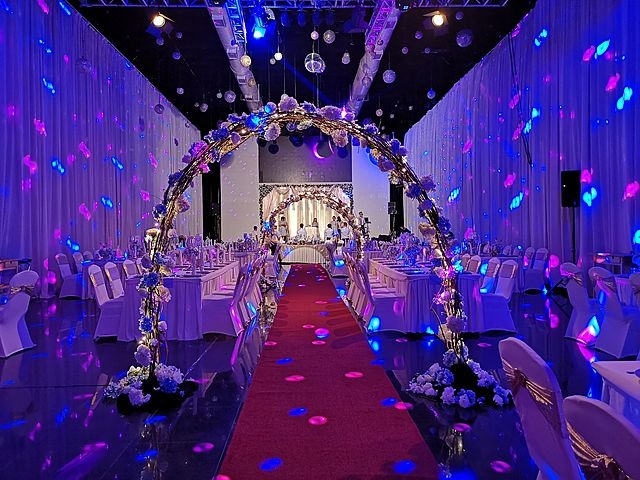 high-ceiling wedding hall with colourful lighting and banquet seating