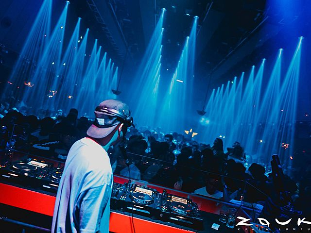 dj playing in large club kuala lumpur with blue spot lighting