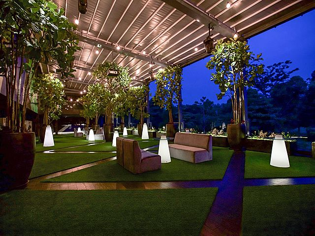 semi-outdoor party area in kuala lumpur decorated with artificial grass and trees surround