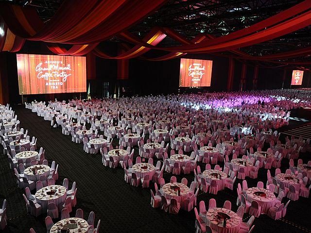 big corporate dining event with round table set up and big stage