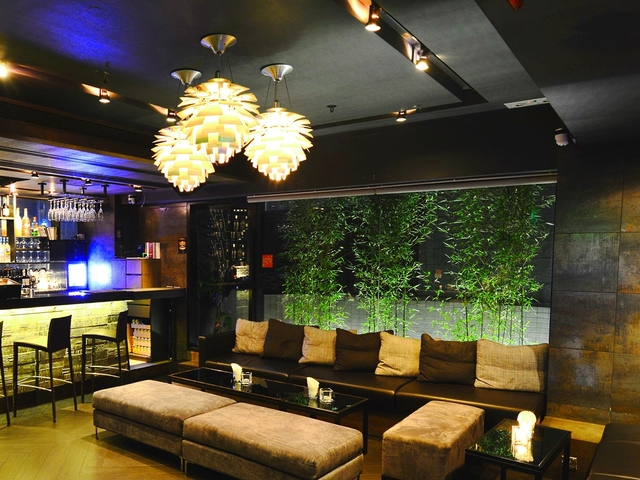 indoor bar area with bamboo plants and sofa tables