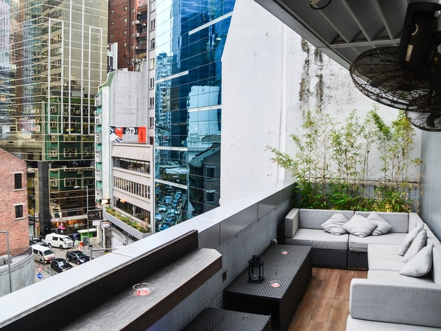 terrace area equipped with sofas and hanging fan on the ceiling