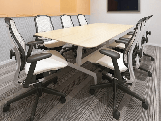 small meeting room with work desk and rolling chairs