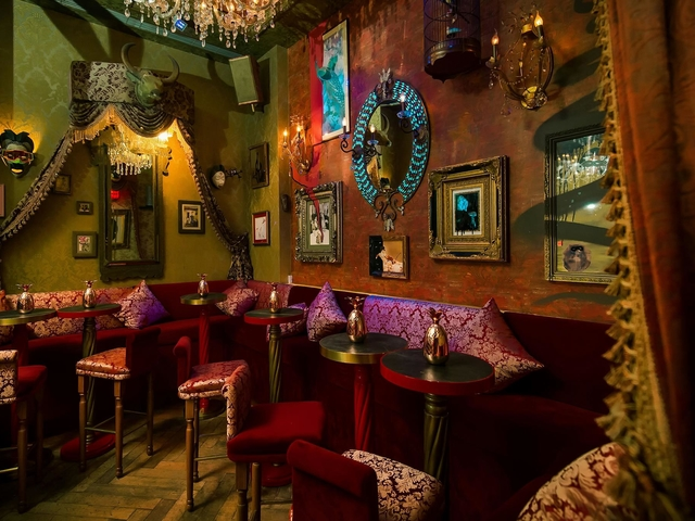 unique bar using red couch and a lot of art decoration on the wall