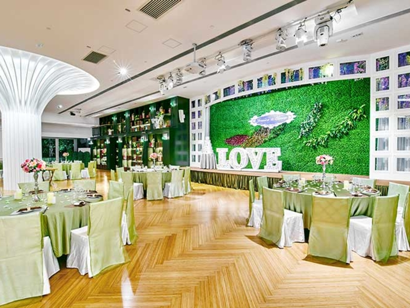 wedding party in the ballroom with garden decoration at the stage
