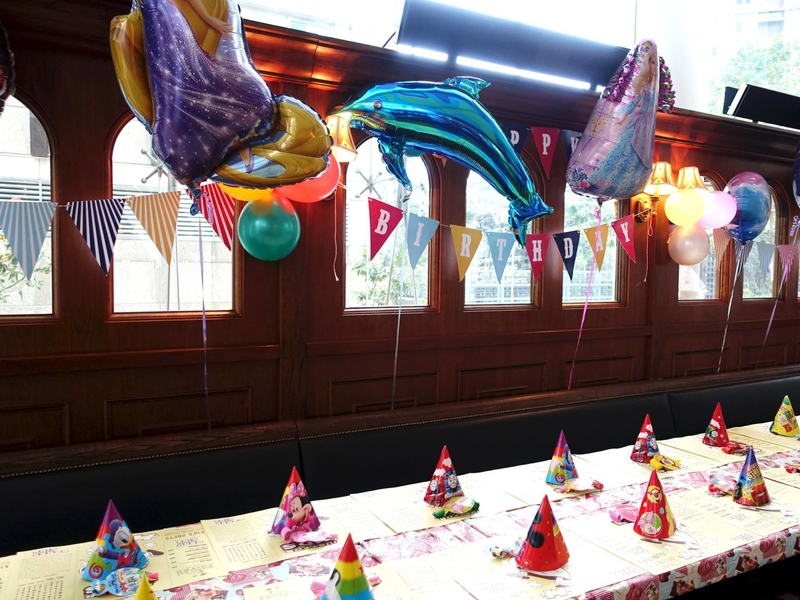 long table setup with balloon decoration and kids birthday party hat on the table
