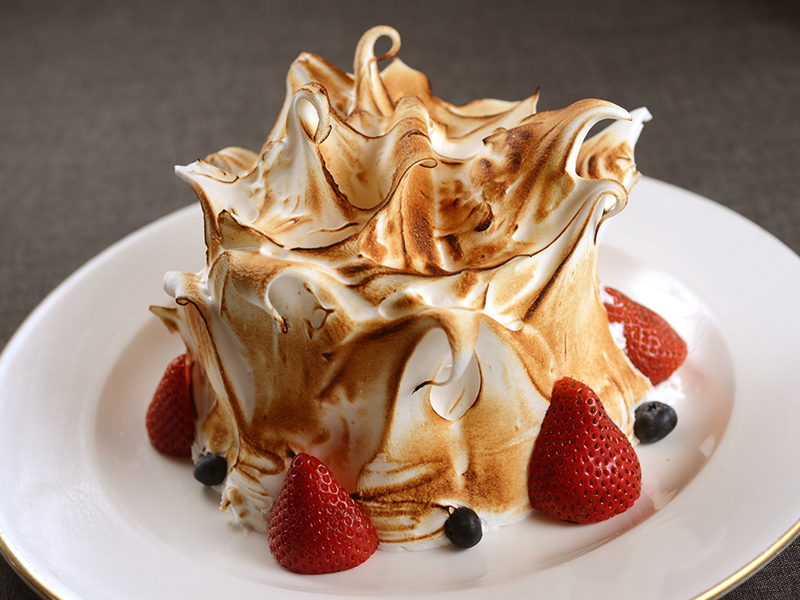 baked alaska made with ice cream, cake and browned meringue