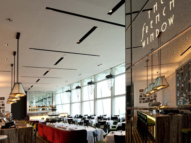 indoor restaurant with double-height floor-to-ceiling windows