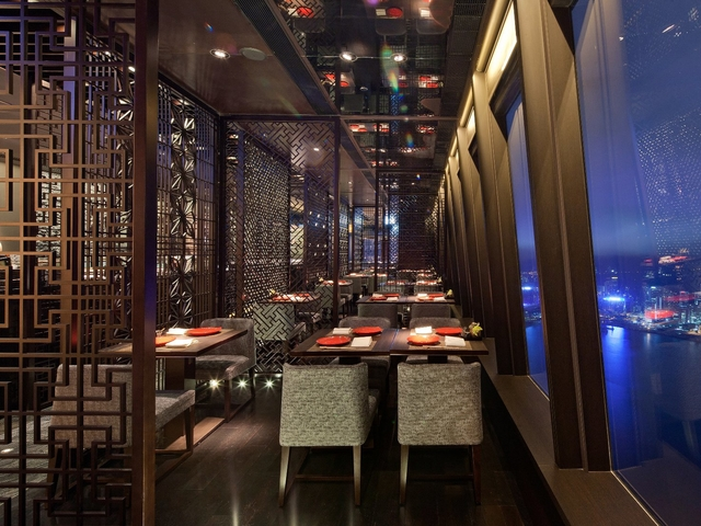 dining are designed with wooden interior and completed with the night view of hong kong city