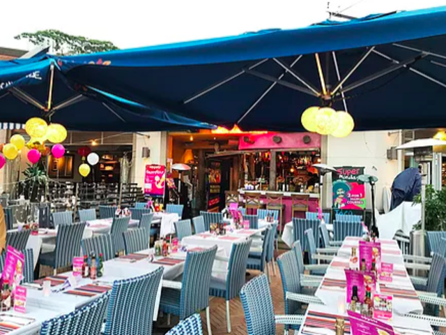 outdoor area setup for hen party decorated with pink and yellow balloons