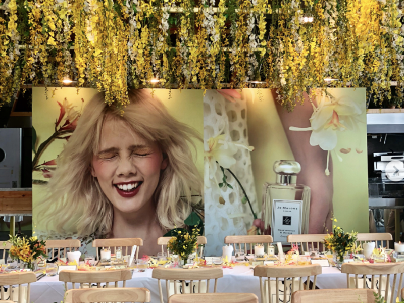 product launch event of parfume brand with woman backdrop and yellow flower decoration