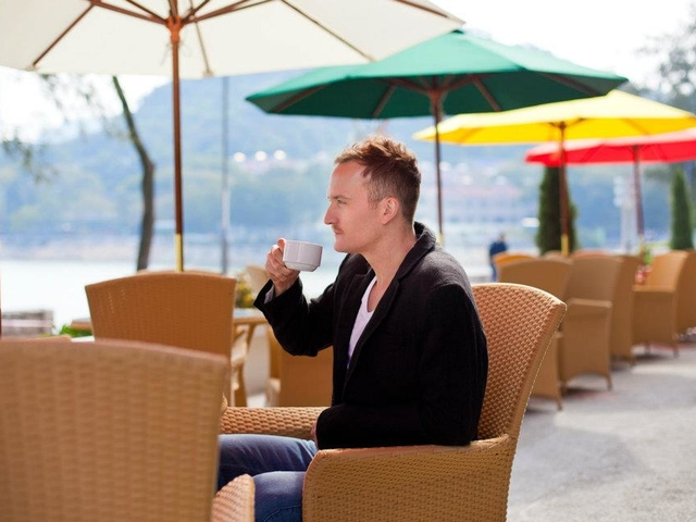a man is enjoying his coffee at the outdoor area with a panoramic view of silvermine bay