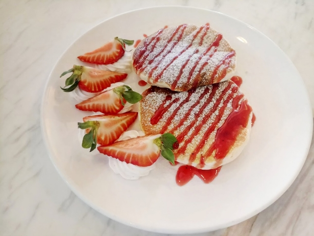 two strawberry pancakes with strawberry slices and jam on the top of the pancakes