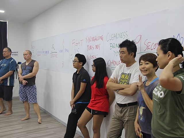 corporate team building group session by 7 people standing in front of the white board