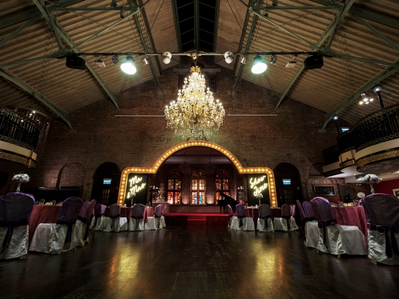 ballroom featuring with stained glass, dark teak paneling and flooring