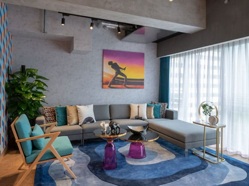 lounge area with natural light and bohemian rhapsody painting on the wall