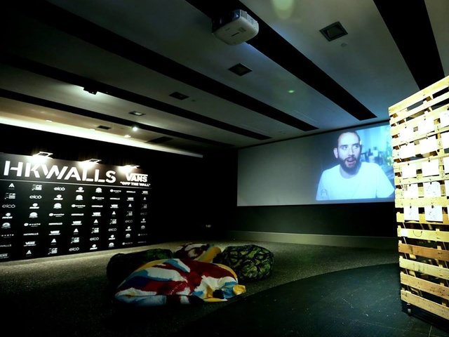 multifunctional event space with giant screen, photo wall, and beanbag