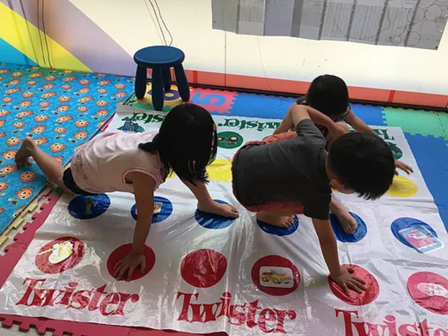kids are playing twister game together on the floor