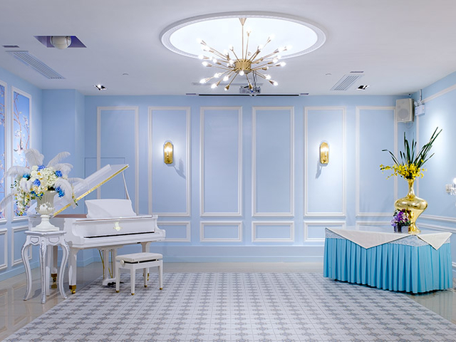 private royal blue room featuring the white grand piano and table for decoration