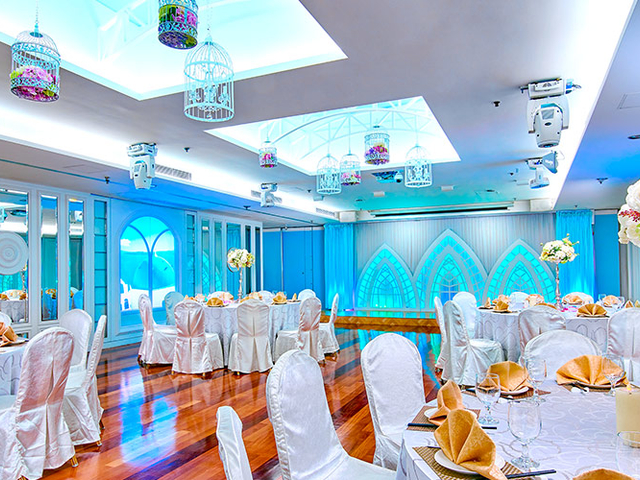 blue themed of ballroom with round table setup and wooden floor