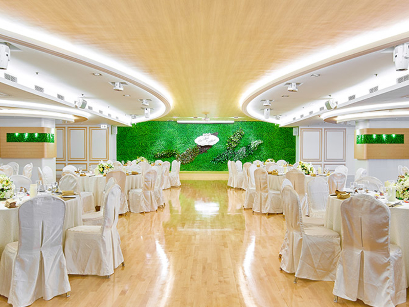 banquet style of ballroom with green backdrop on the stage