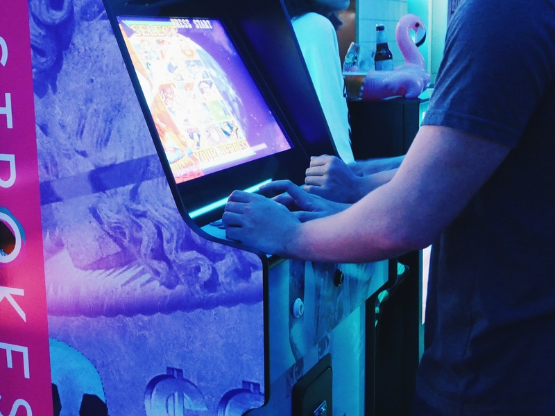 player playing on game machine in strokes mini golf bar