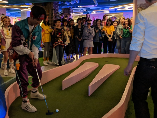 player hitting golf ball with golf club in a mini golf deck