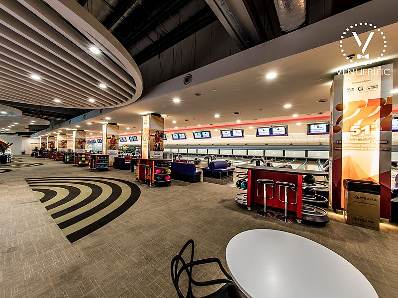 large bowling alley hallway area with table and chairs