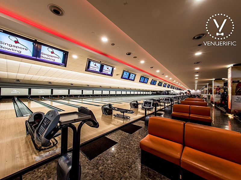 bowling alley with score screen and brown long couch