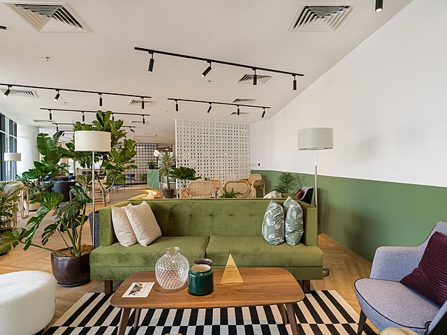 green theme venue with artificial plant and sofa