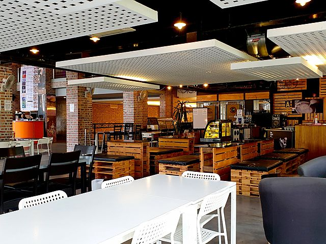 large restaurant with white square ceiling and some wooden tables