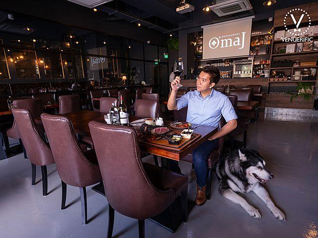 customer enjoying wine with his husky in omaj pet friendly restaurant singapore