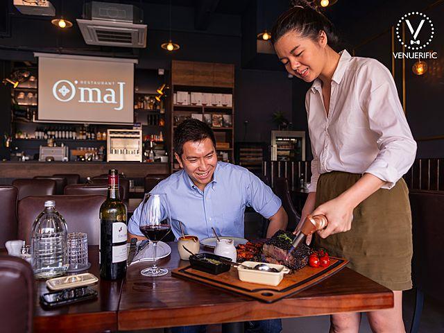 Omaj restaurant server help prepare steak for customers