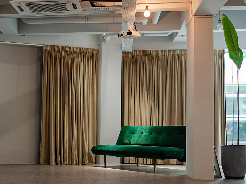 function room with green couch and beige drape