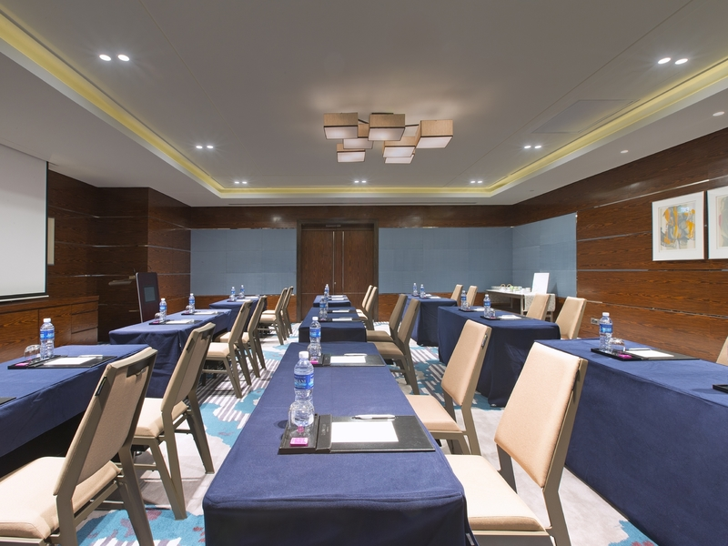 medium scale workshop venue with long blue table and mineral water on it