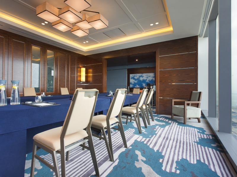 meeting space with long blue table and square pendant lights