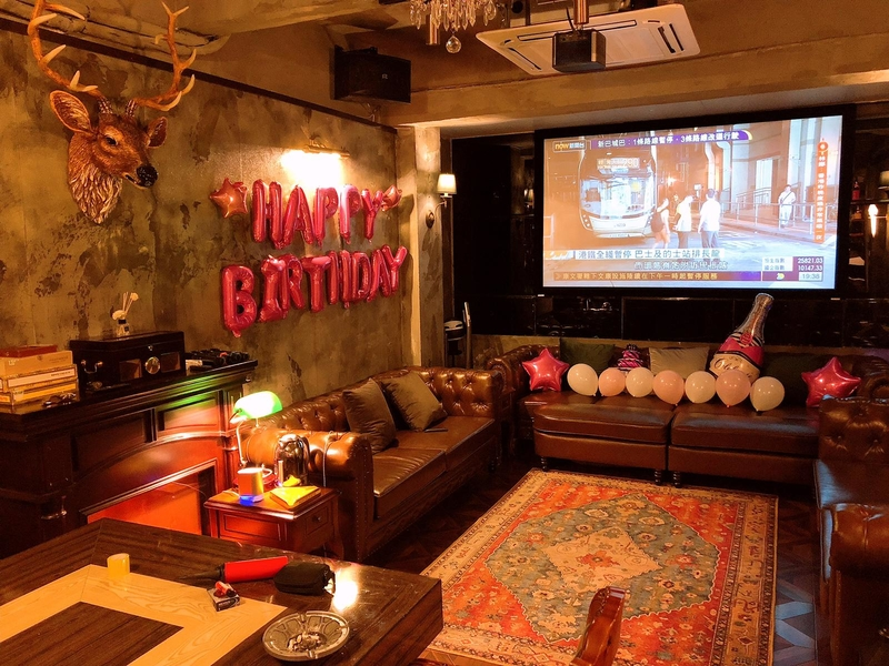lounge area with projector screen with birthday party setup