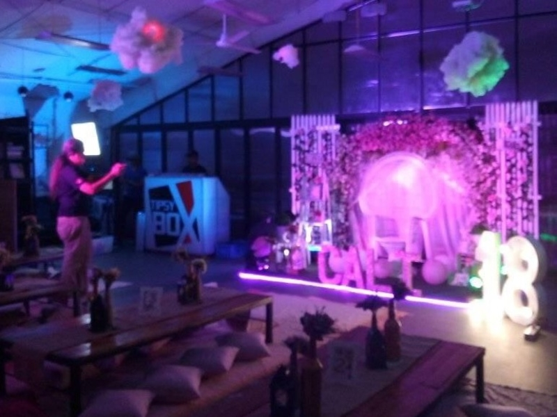 18th birthday venue in makati decorated with purple lights and low tables