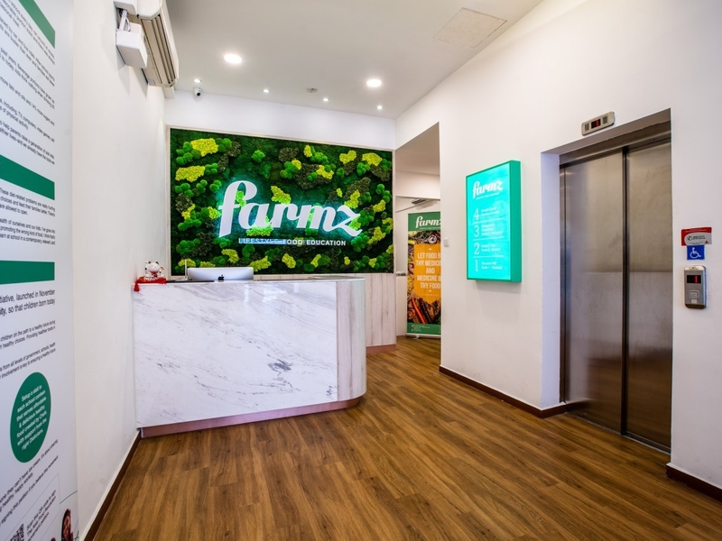 reception area with green theme of farmz neon sign on the wall