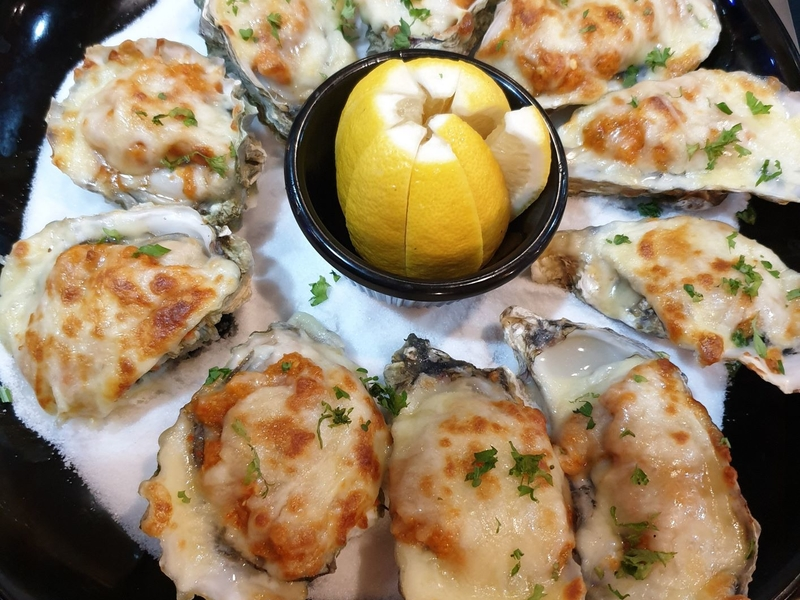 baked oyster served on the plate with limes