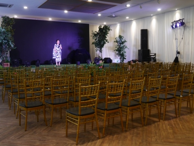 chairs set up for music performance event with purple stage