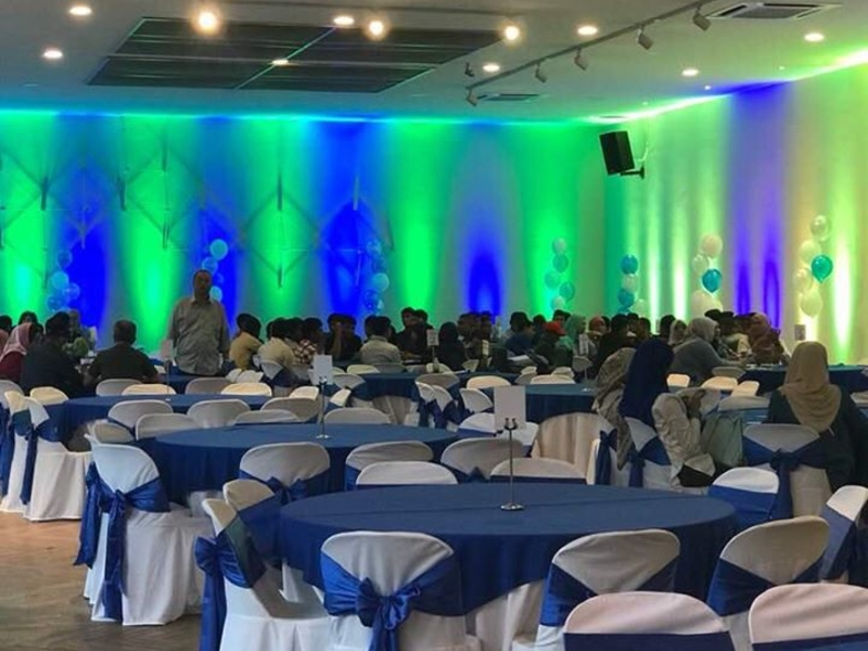 event set up with round table and decoration with green and blue lighting