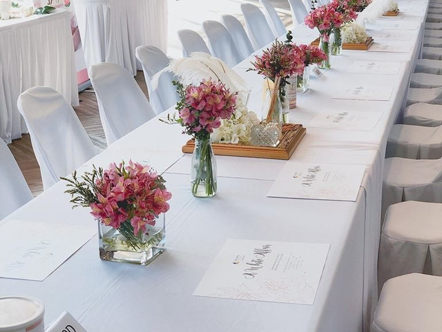 long table set up for wedding with white mat with pink flower
