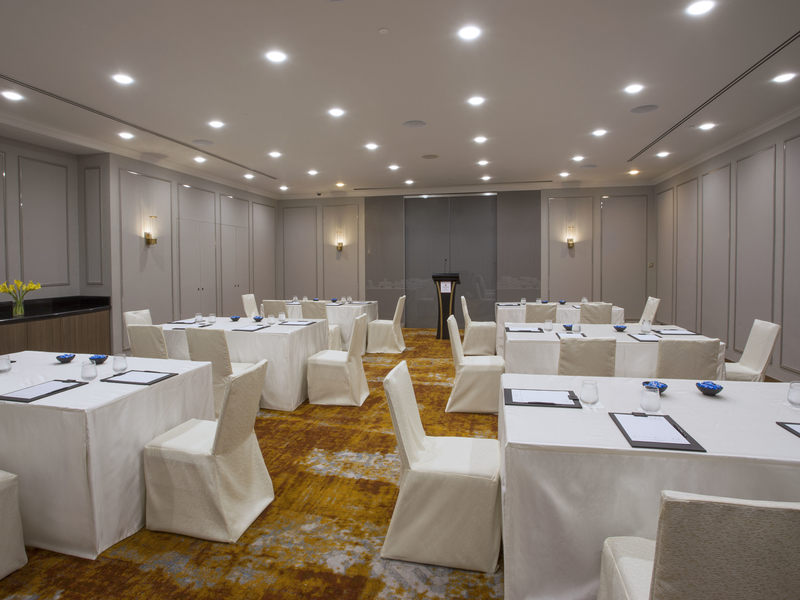 corporate meeting table set up with white dominant in room with high ceiling